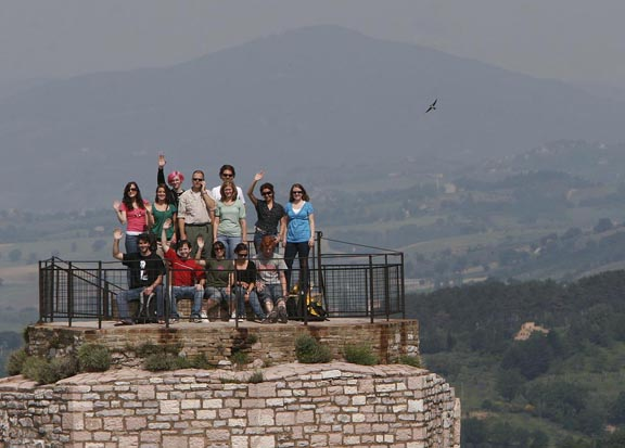 To make group photos dynamic, find an interesting background. Put people on different levels instead of lining them up. In Assisi, Italy, my group was exploring a medieval castle. When they all popped up on a distant turret, I put on a long lens and made an international cell phone call to get them to look my way.