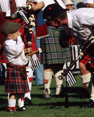 Take active photos of people doing real things. Your relatives can only stand so many photos of children, even cute ones. At a Celtic festival in France, this pipe band let me hang out with them. But the real moment came when I stepped back and let them interact with each other. This kid was adorable, but even cuter when the guys told him jokes to calm his nerves before the performance.