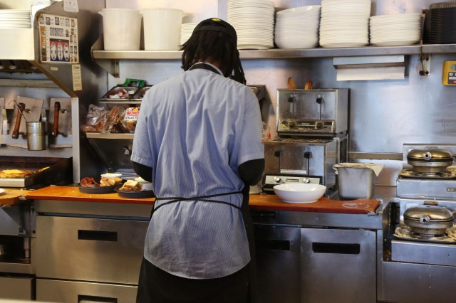 Aaron Johnlewis, a line cook, prepares to go orders at Waffle House.